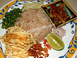 Place shrimp paste fried rice on a plate and serve with side ingredients