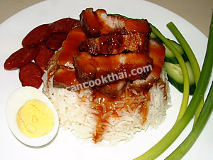 Put rice on a plate, top with crispy pork and pour the sauce over, serve with cucumber, green onion, boiled egg, and fried Chinese sausage
