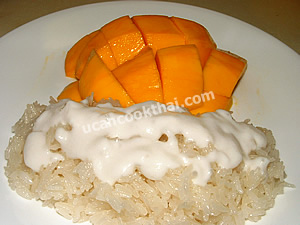Put sweet glutinous rice in a plate, top with coconut cream and serve with ripe mangoes