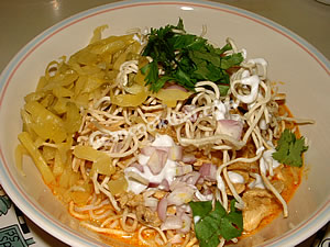 Put the egg noodles in a bowl, pour curry sauce, add sliced pickled mustard and diced shallots, top with crispy egg noodles, cilantro leaves, and coconut cream, then serve hot