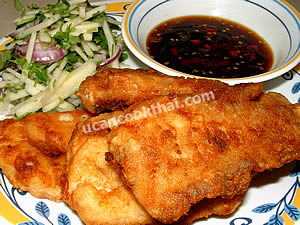 Put fried fish fillets on a plate, serve with apple salad and spicy dressing