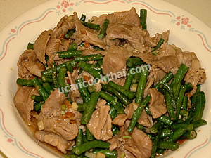 Place stir-fried pork with long green beans and salted soy bean on a plate and serve immediately