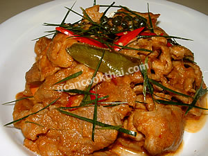 Place stir-fried pork with red curry paste on a plate, sprinkle with finely sliced kaffir lime leaves, and serve immediately