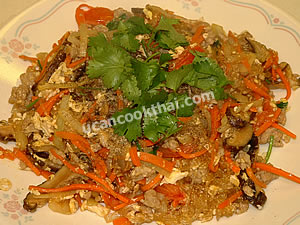 Place stir-fried mung bean noodles and ground pork on a plate, sprinkle with chopped cilantro, and serve immediately