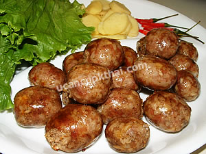 Put Thai Style Sausages on a plate, serve with lettuce leaves, sliced ginger and fresh chilies