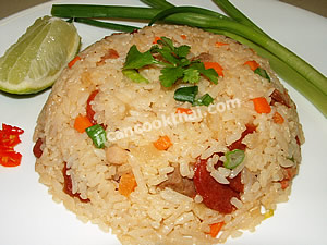 Put the fried rice on plate, serve with green onion, sliced chilies, and a wedge of lime