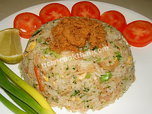 Put imitation crabmeat fired rice on a plate, top with dried pork fluff, then serve with sliced tomatoes, green onion and a wedge of lime