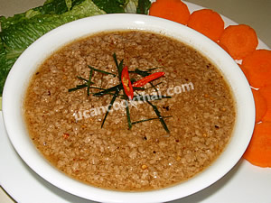 Put spicy ground pork dip in a bowl, garnish with sliced kaffir lime leaves and chilies, then serve with fresh vegetable