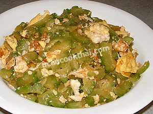 Place stir0fried bitter gourd with eggs on a plate and serve immediately